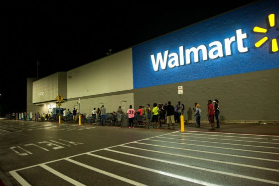 People begin lining up at a closed Wal-Mart store in Beaumont, TX at around 2:30 Thursday morning after hearing the water supply for the city had failed.